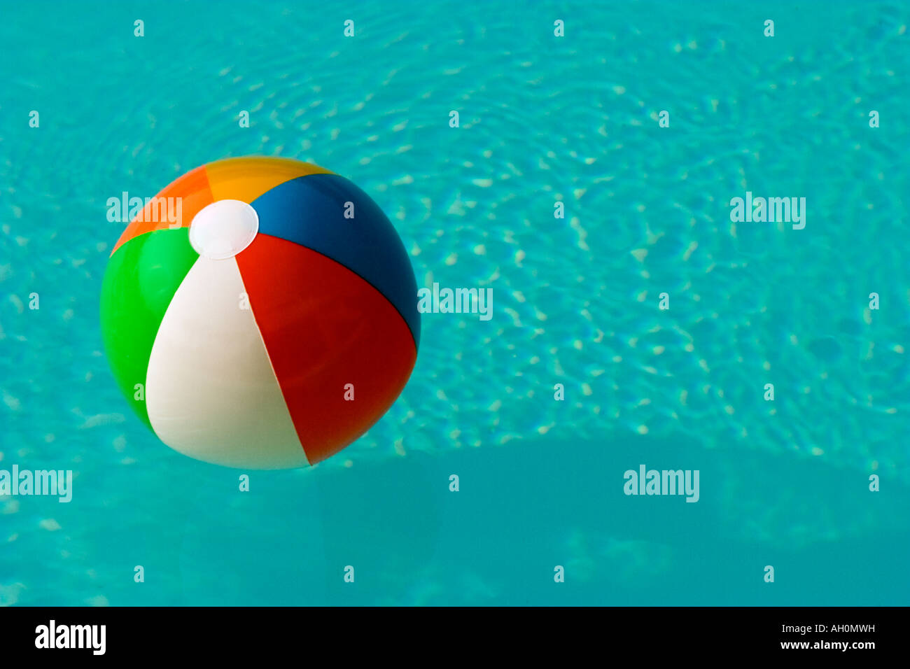 Pool Water With Beach Ball colourful beach ball floating in a swimming pool with bright blue