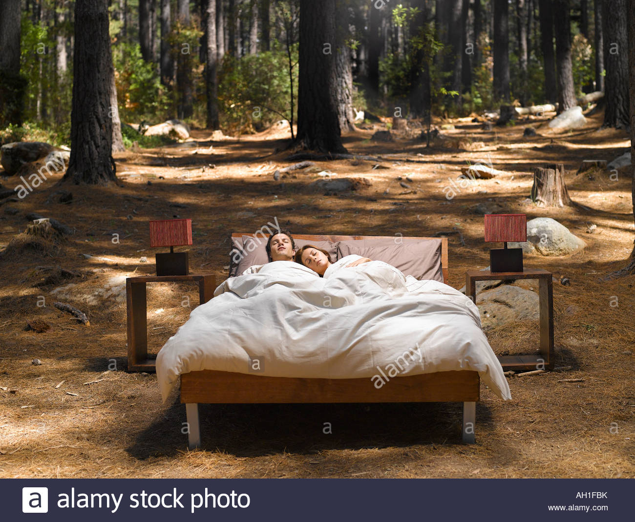A Couple Sleeping In A Bed Outdoors In The Woods Stock