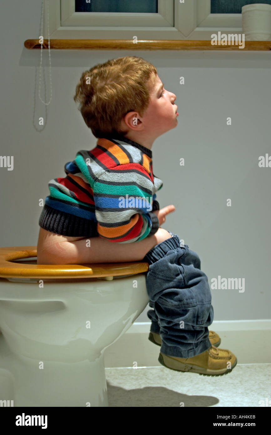 young boy and the toilets Stock Photo - Young boy child sitting on the loo toilet lavatory or bog from the side with multi coloured jersey or jumper NAOH
