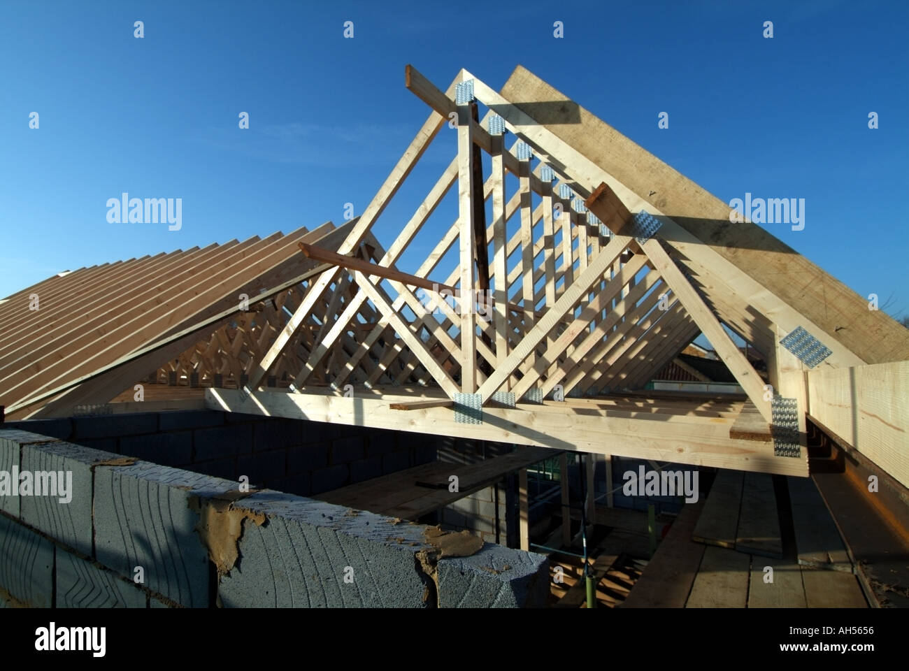 Detached house work in progress fixing prefabricated roof for Prefabricated wood trusses