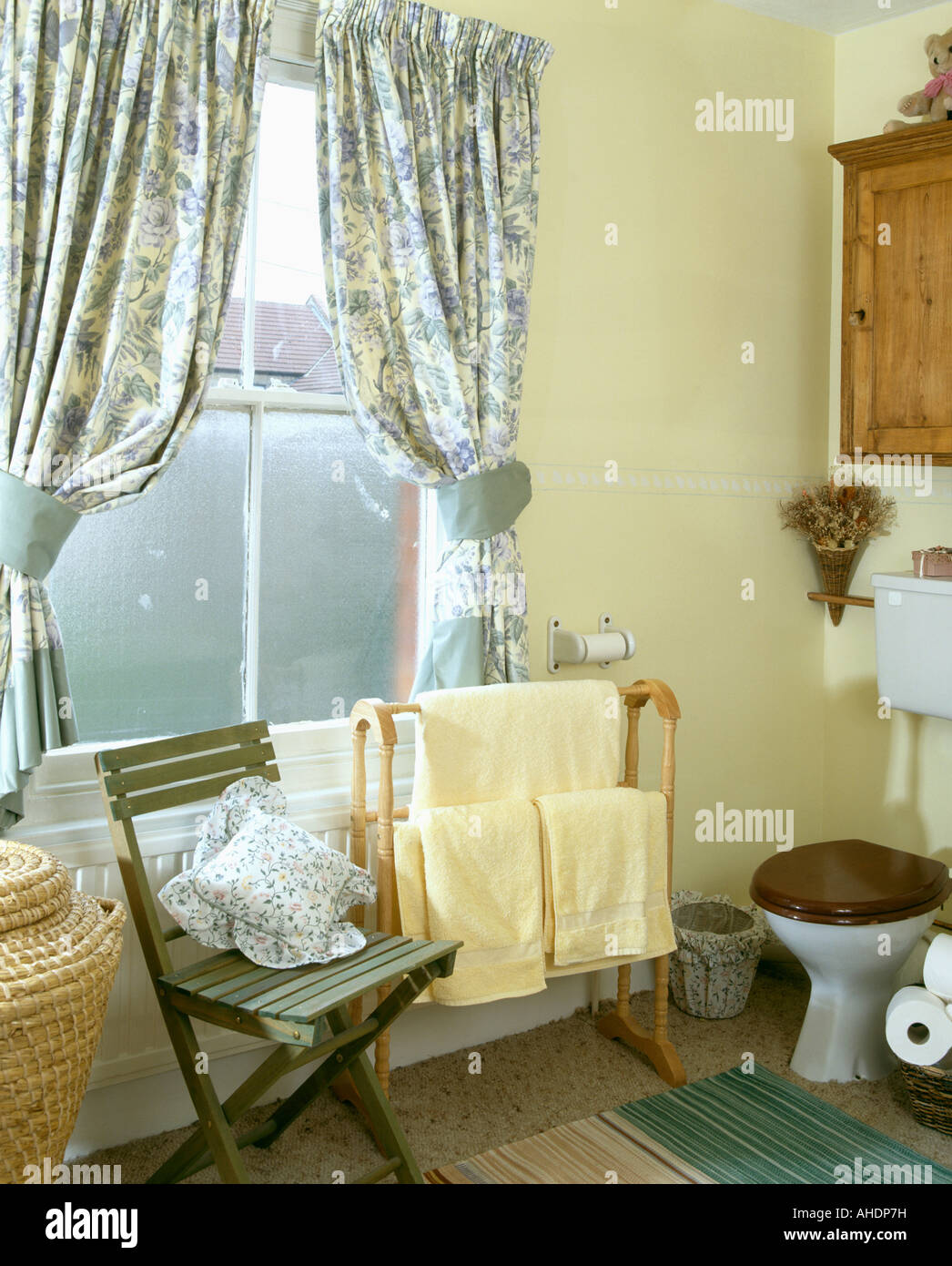 Blue Floral Curtains With Tiebacks In Pale Yellow Bathroom With Yellow  Towels On Wooden Towel Rail
