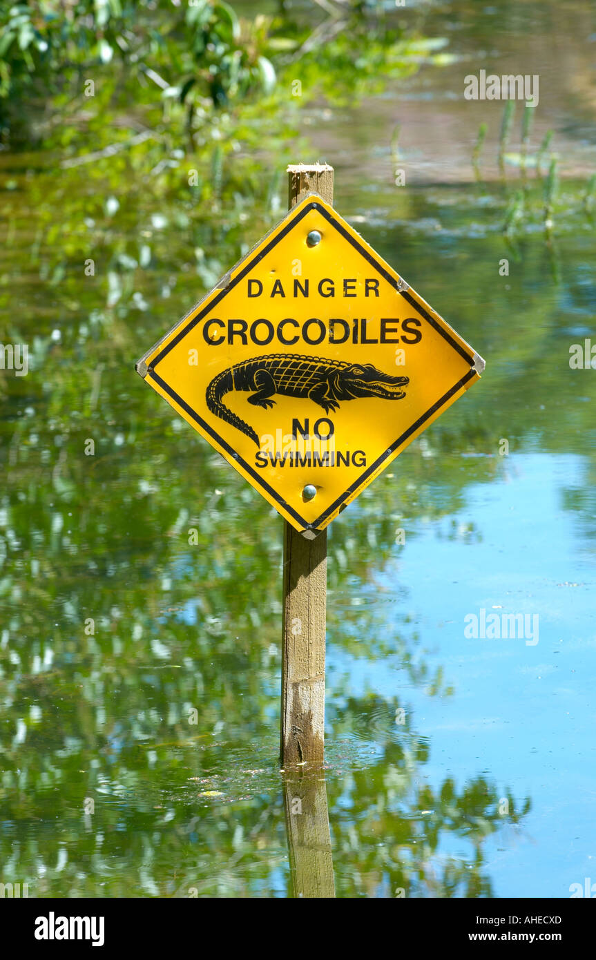 danger crocodiles no swimming sign in water stock photo