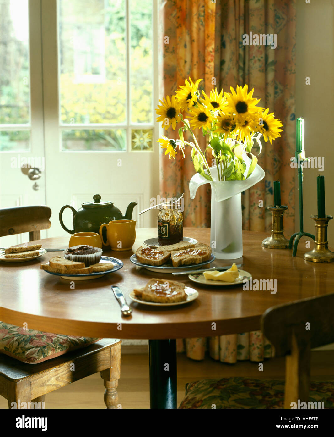 dining room with yellow sunflowers in glass vase on circular wood