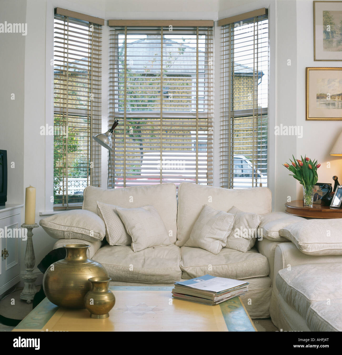 cream sofa in front of bay window with slatted blind in living room with  brass pots on coffee table