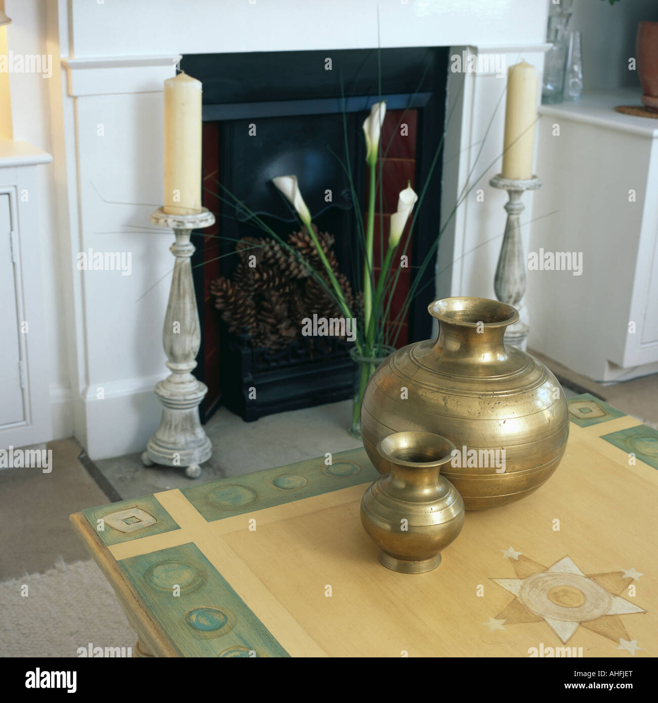 brass turkish pots on table in front of fireplace with candles in