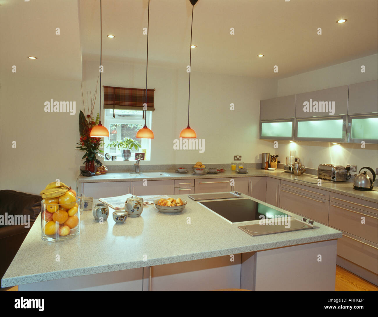 Pendant lights over island unit with halogen hob and oranges in glass jar  in modern white kitchen