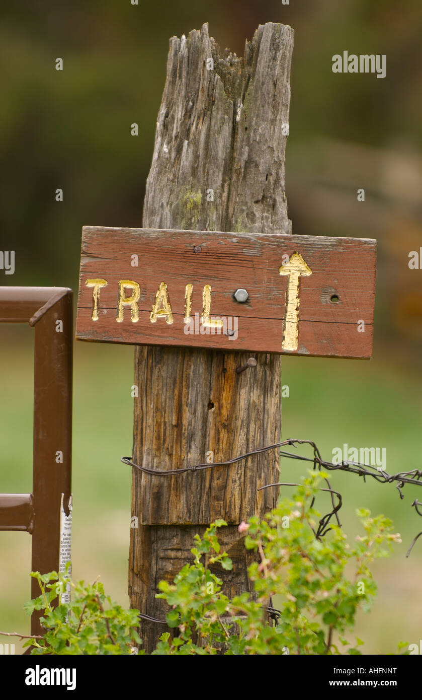 stock photo wooden trail sign with an arrow on a wooden fence post
