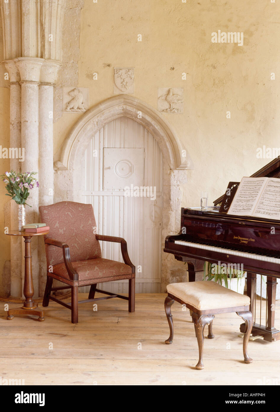 grand piano and antique chair beside gothic door in large living