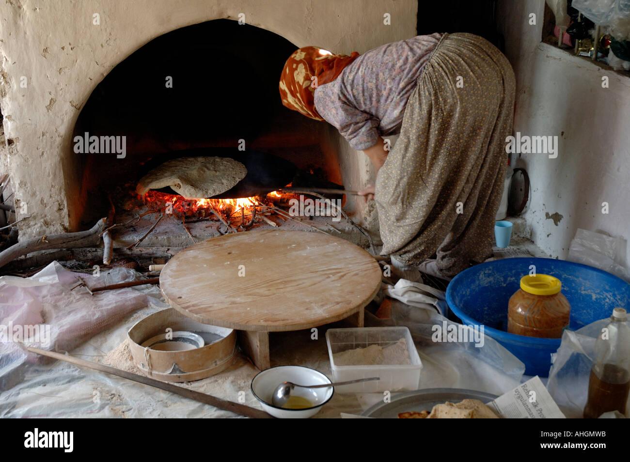 Turkish woman making flat bread in fireplace in home near village ...