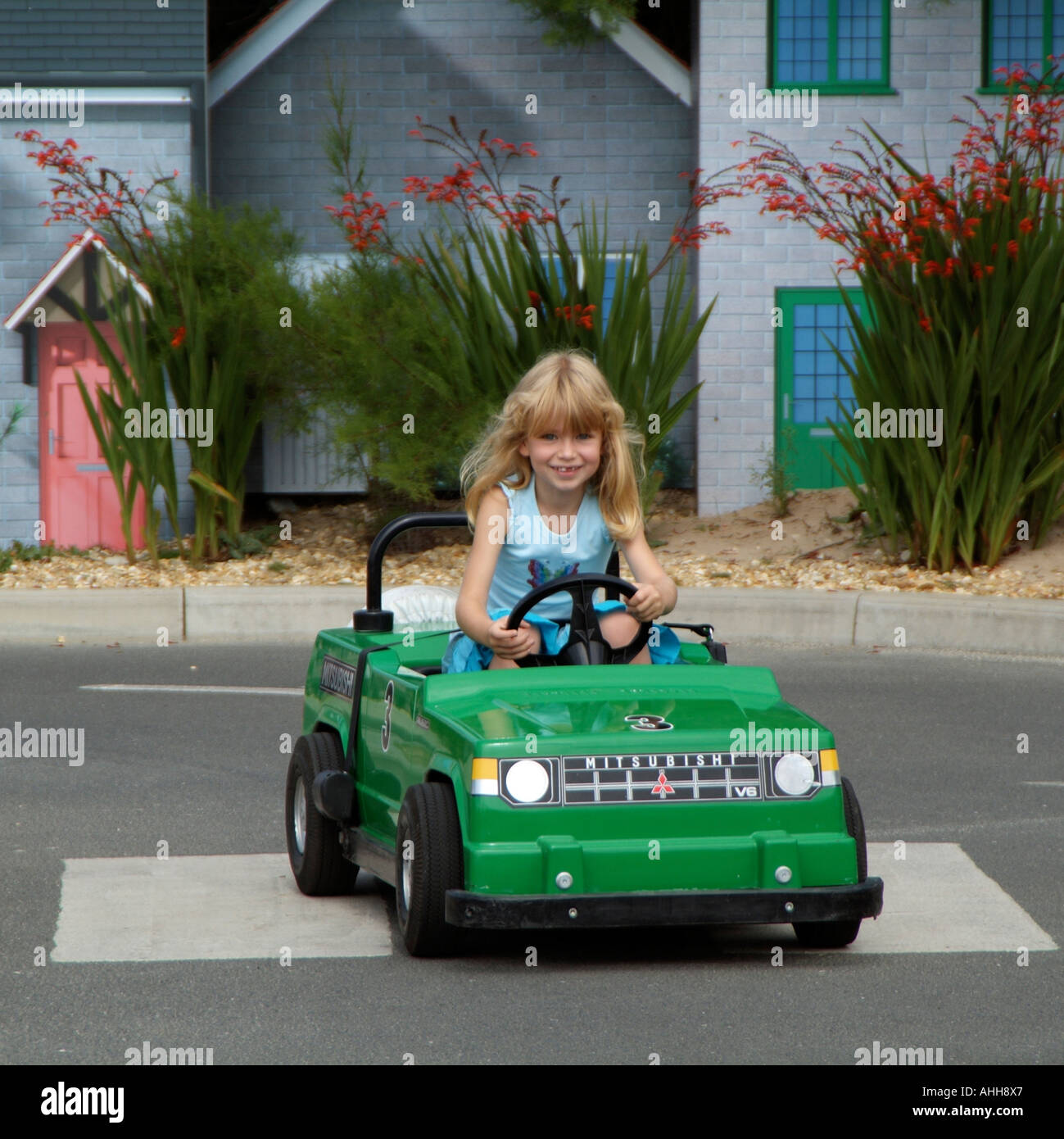 driving lessons for children kids learning the rules of the road using electric cars blonde girl driving a green car