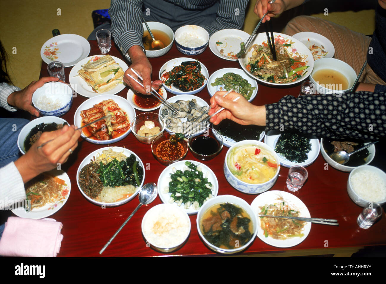 Dinner table with food - Family Sitting At Dinner Table Eating Variety Home Made Korean Foods