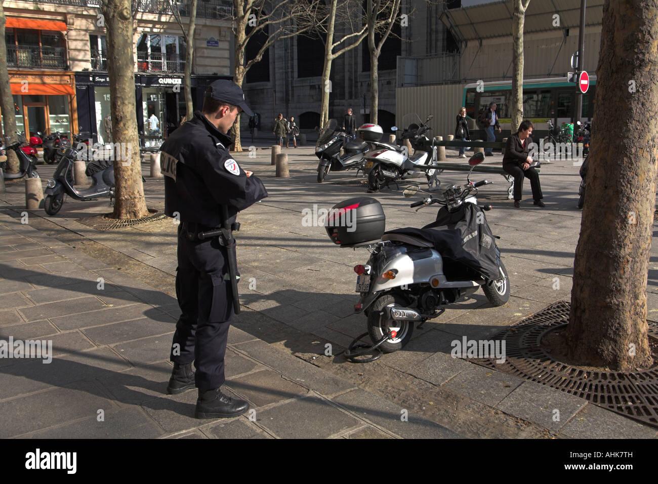 paris france traffic cop gendarme writes parking ticket for scooter stock photo royalty free. Black Bedroom Furniture Sets. Home Design Ideas