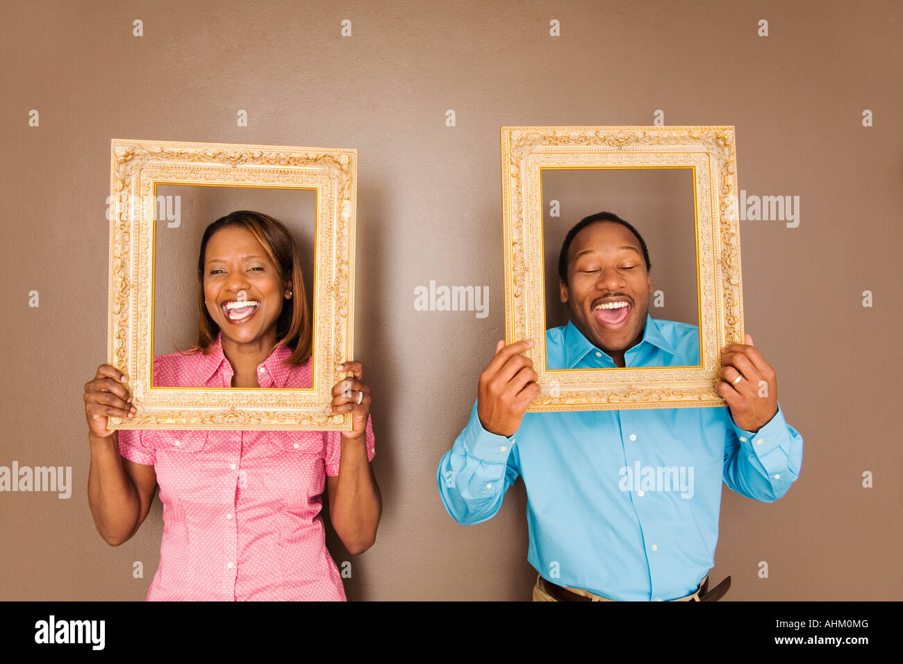 African couple looking through picture frames stock photo royalty african couple looking through picture frames jeuxipadfo Choice Image