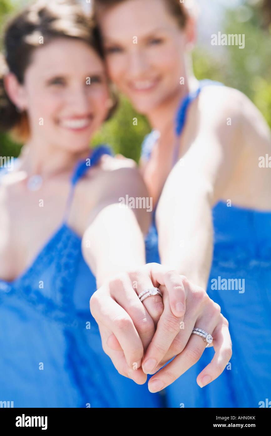 stock photo newlywed lesbian couple displaying wedding rings lesbian wedding bands Newlywed lesbian couple displaying wedding rings