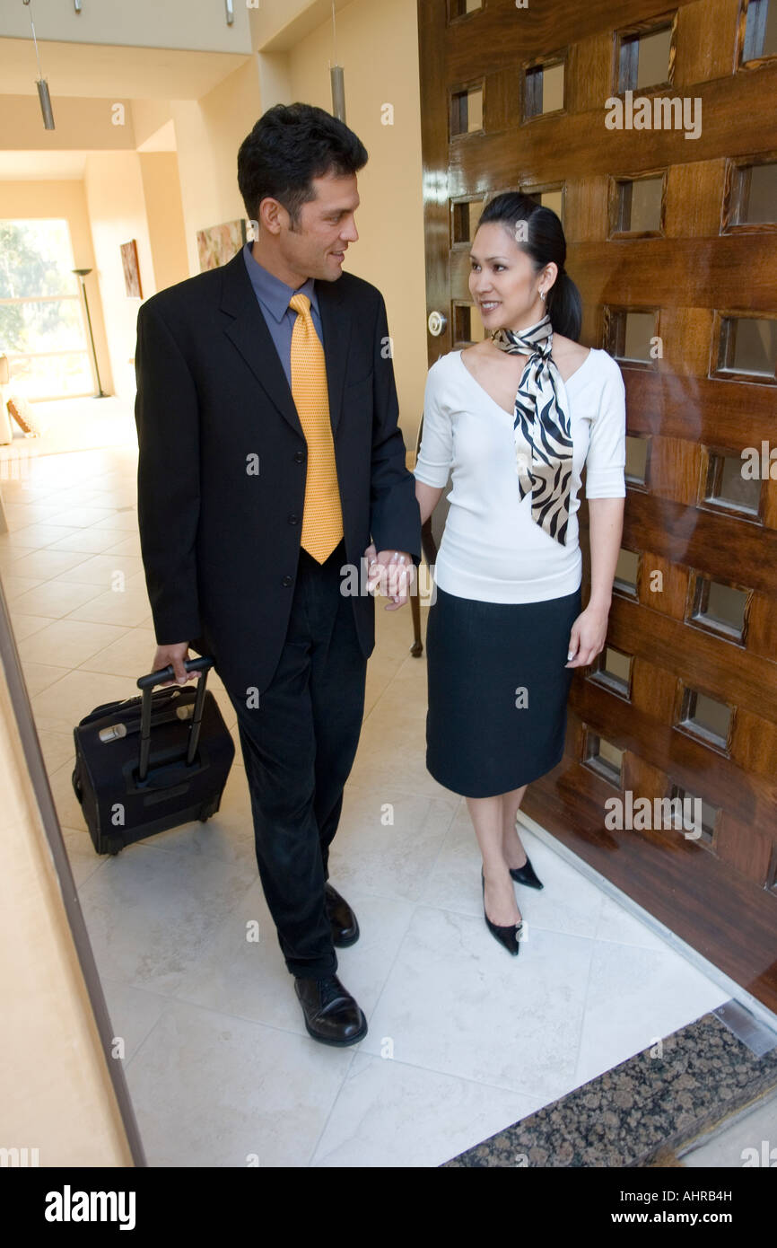 A business man and woman walking out the door to go to work Stock