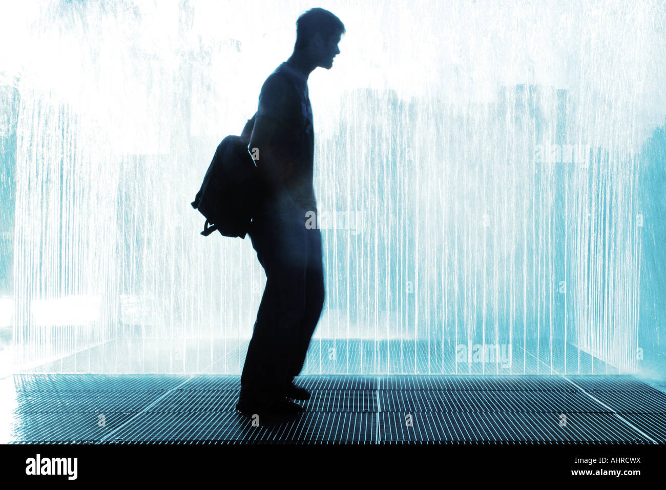 Silhouette Of A Man Standing In Water Fountain To Cool Down