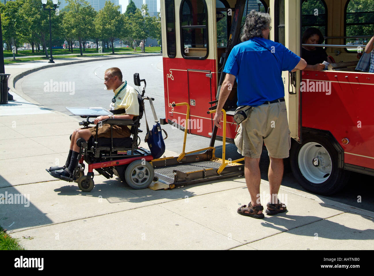 Handicapped male in a wheel chair boards a special needs bus at ...