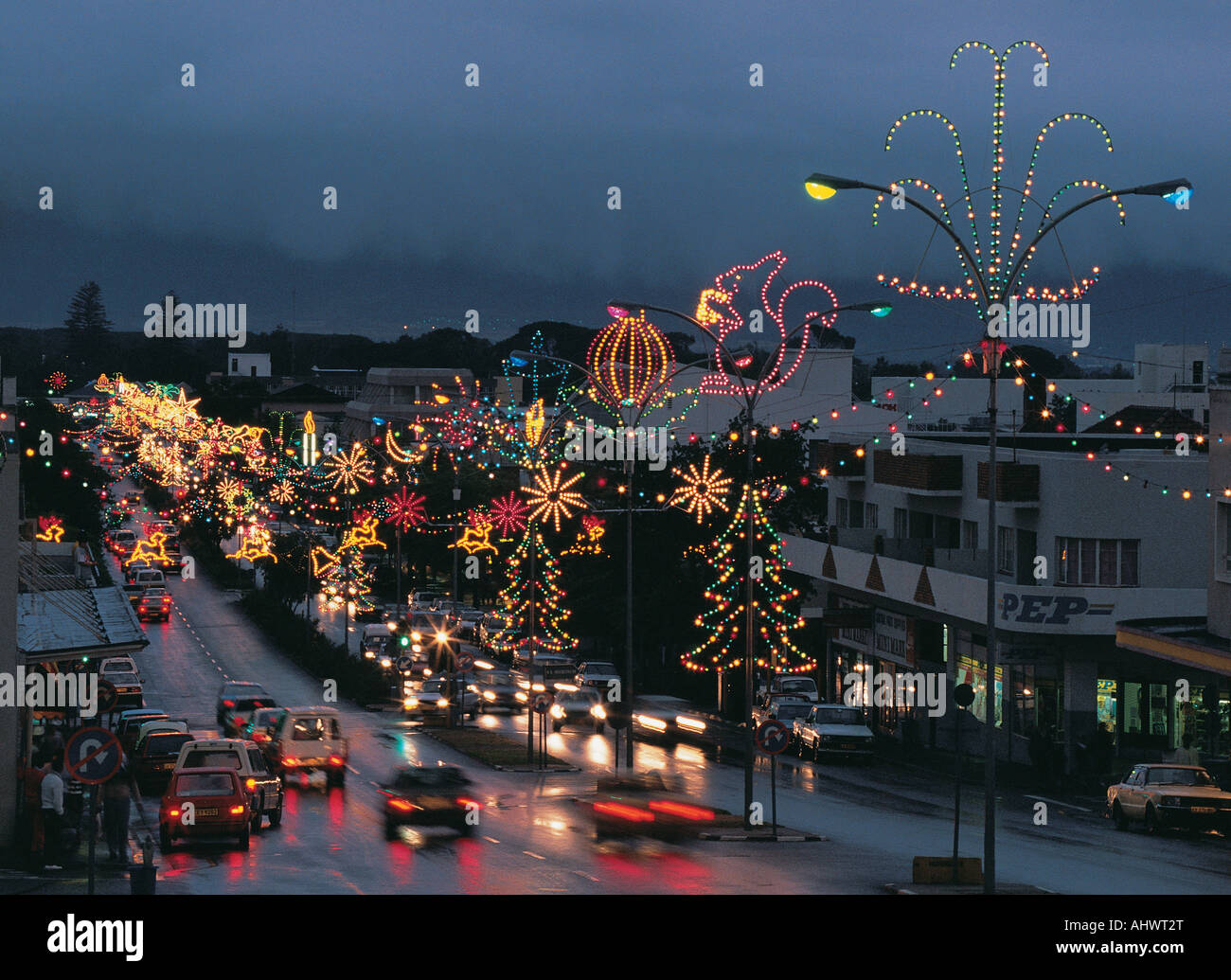 Christmas lights and decorations on a wet street busy with ...