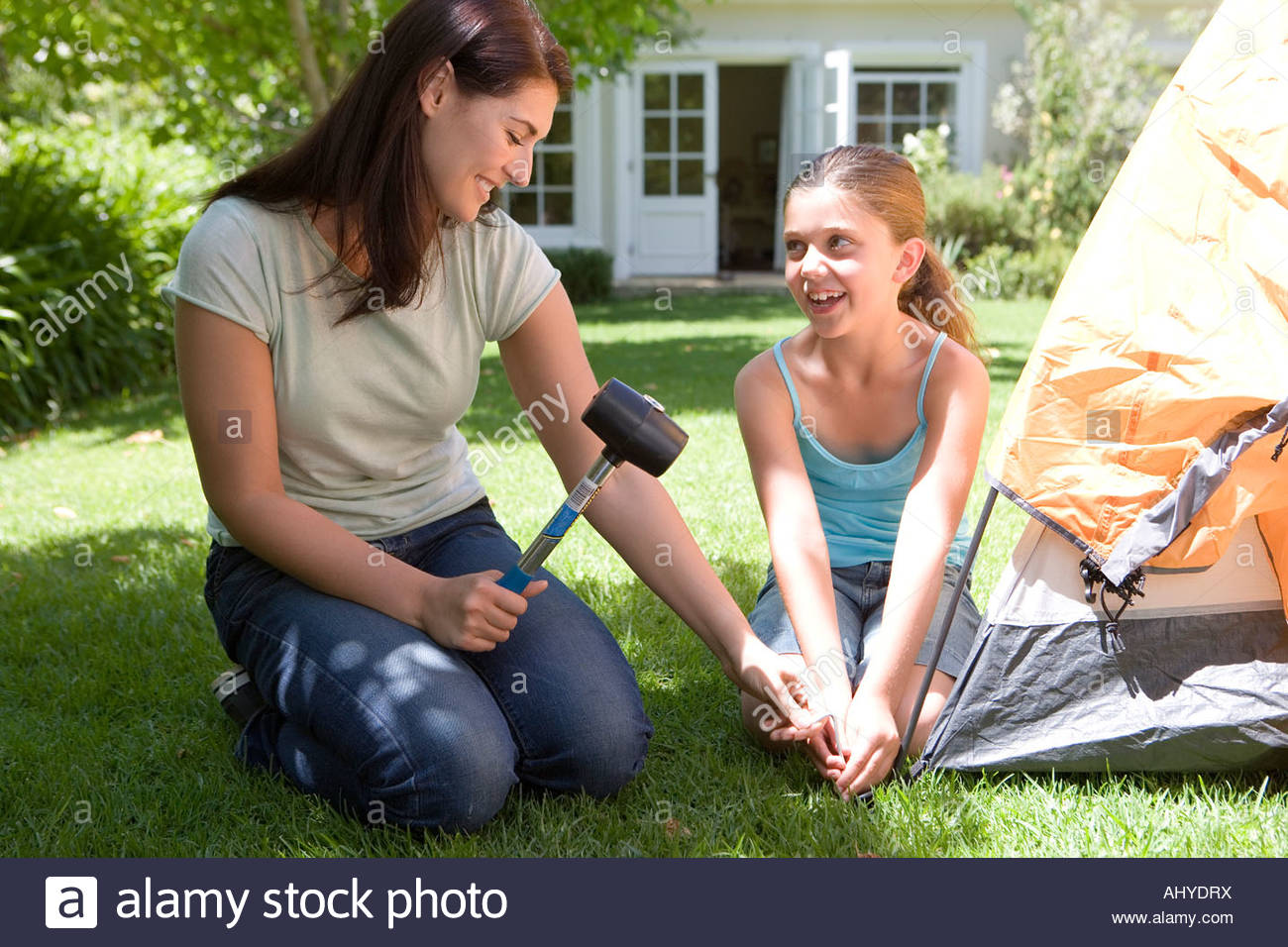 Mother and daughter 8 10 assembling tent on garden lawn woman hammering tent peg into grass with mallet smiling  sc 1 st  Alamy & Mother and daughter 8 10 assembling tent on garden lawn woman ...