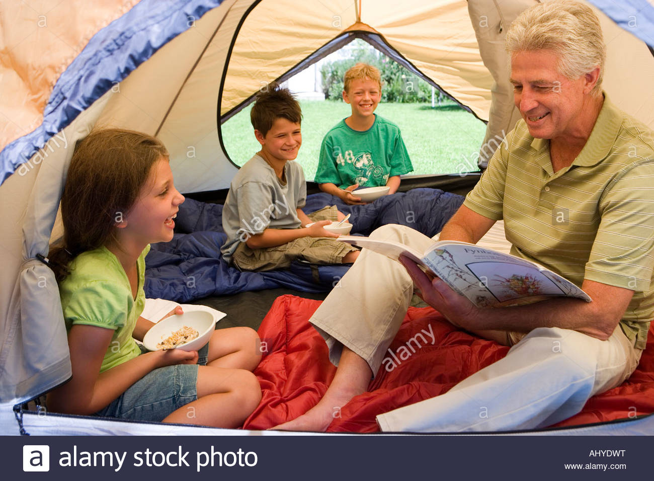 Family sitting inside tent on garden lawn children 8 10 eating breakfast grandfather reading magazine smiling  sc 1 st  Alamy & Family sitting inside tent on garden lawn children 8 10 eating ...