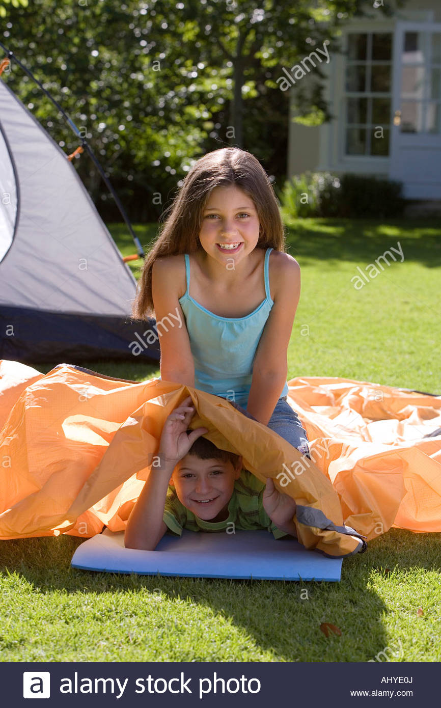 Boy and girl assembling tent in garden girl sitting on top of boy lying beneath outer tent canvas smiling portrait  sc 1 st  Alamy & Boy and girl assembling tent in garden girl sitting on top of boy ...