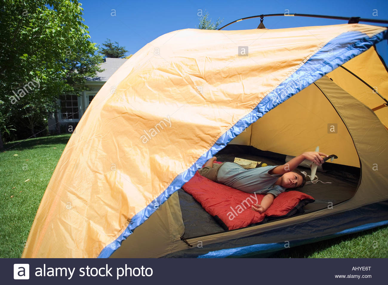 Boy 8 10 lying on red sleeping bag inside orange tent on garden lawn playing with toy aero plane rear view & Boy 8 10 lying on red sleeping bag inside orange tent on garden ...