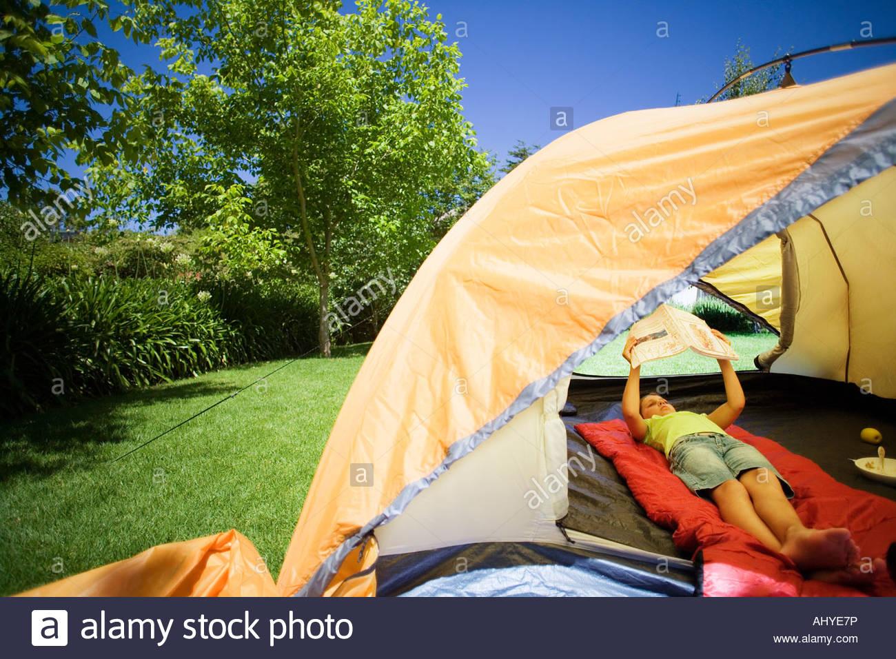 Girl 8 10 lying on red sleeping bag inside orange tent on garden lawn reading book & Girl 8 10 lying on red sleeping bag inside orange tent on garden ...