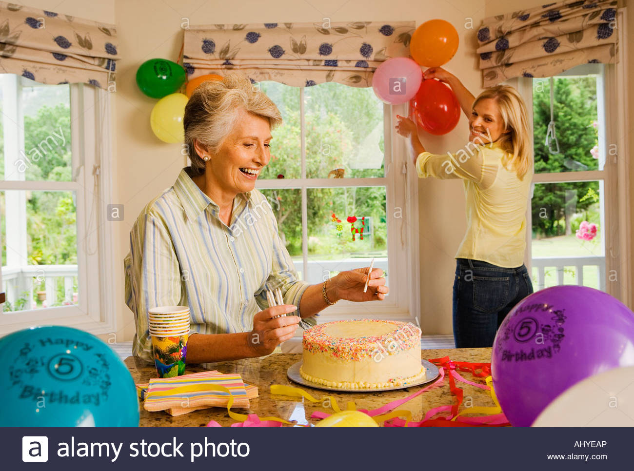 Senior woman and adult daughter preparing birthday party at home Stock ...