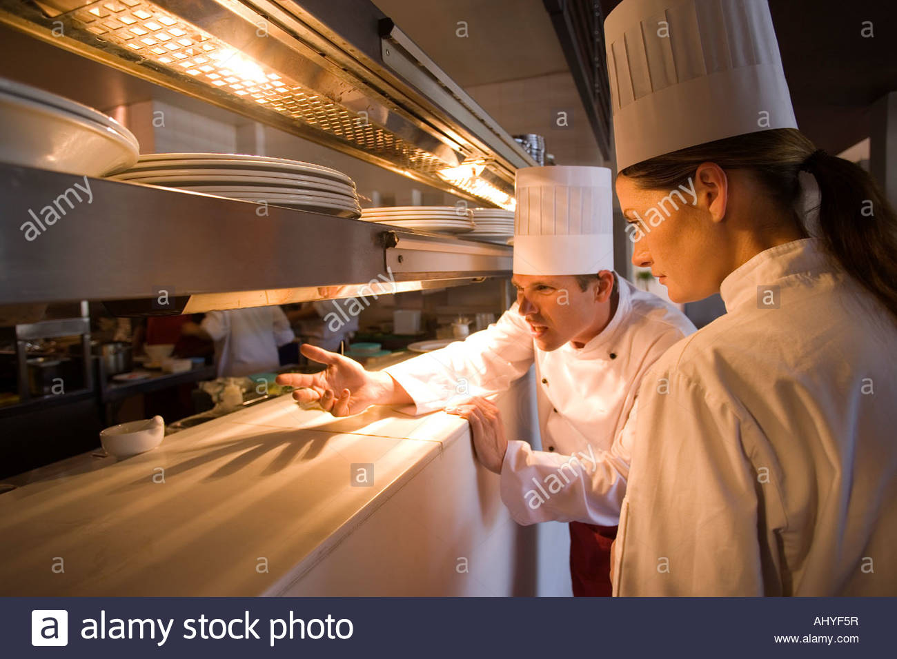 Male And Female Chefs Standing At Order Counter In