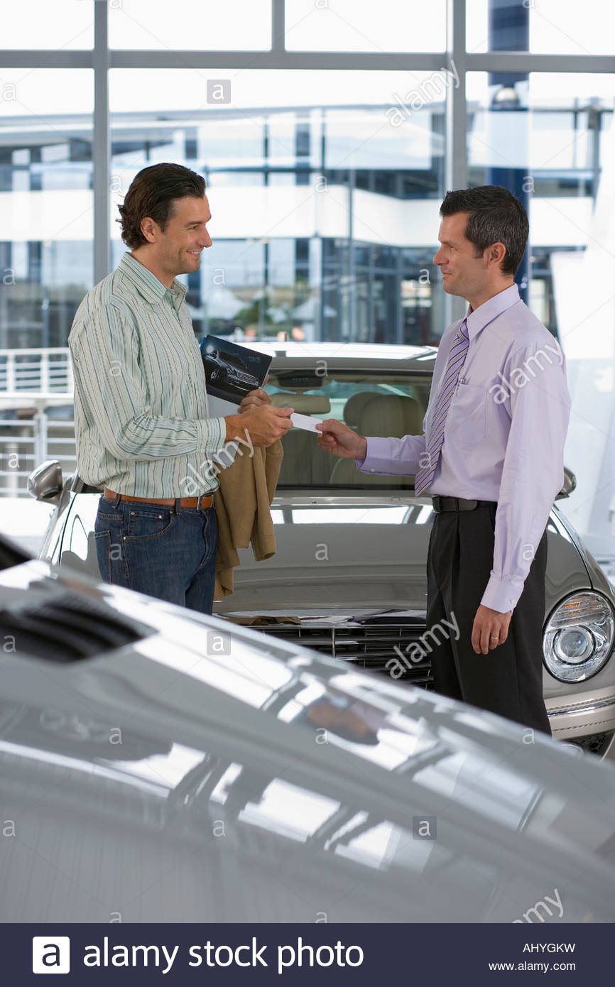 Car salesman passing business card to male customer in showroom ...