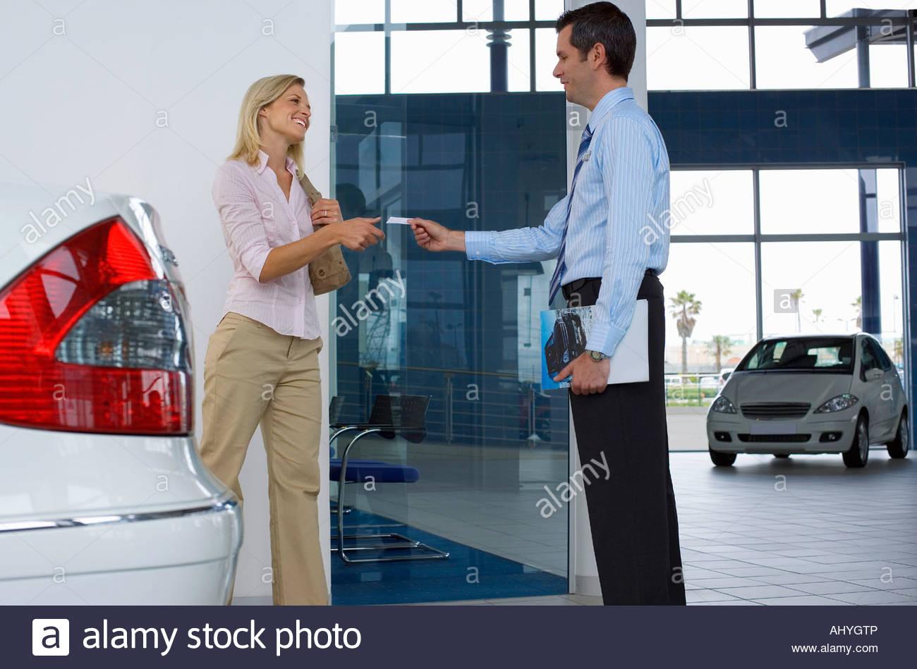 Car salesman passing business card to female customer in showroom ...