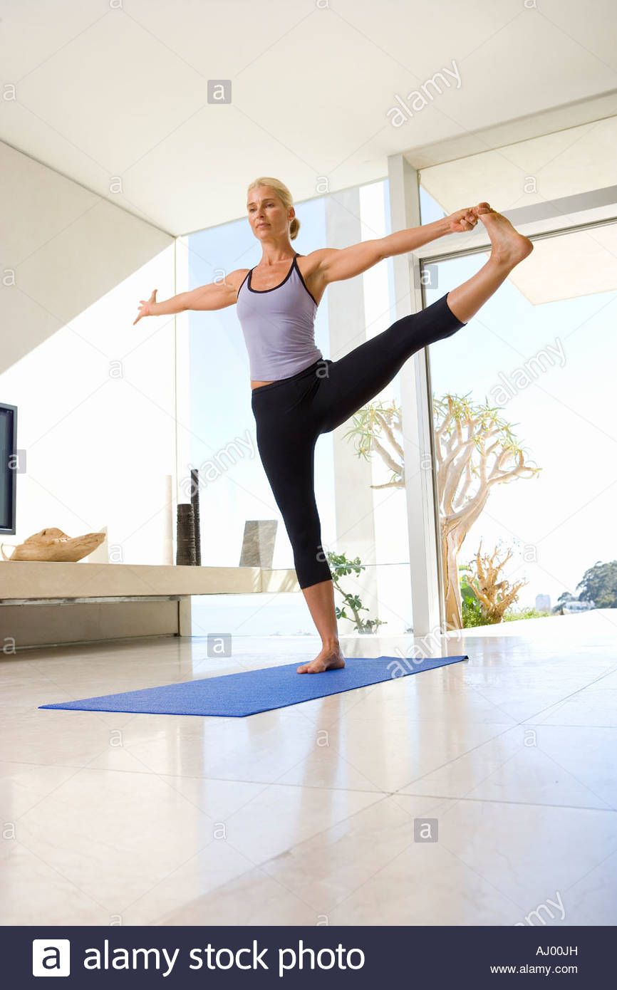 Mature Woman In Yoga Stance On Exercise Mat Living Room Low Angle View