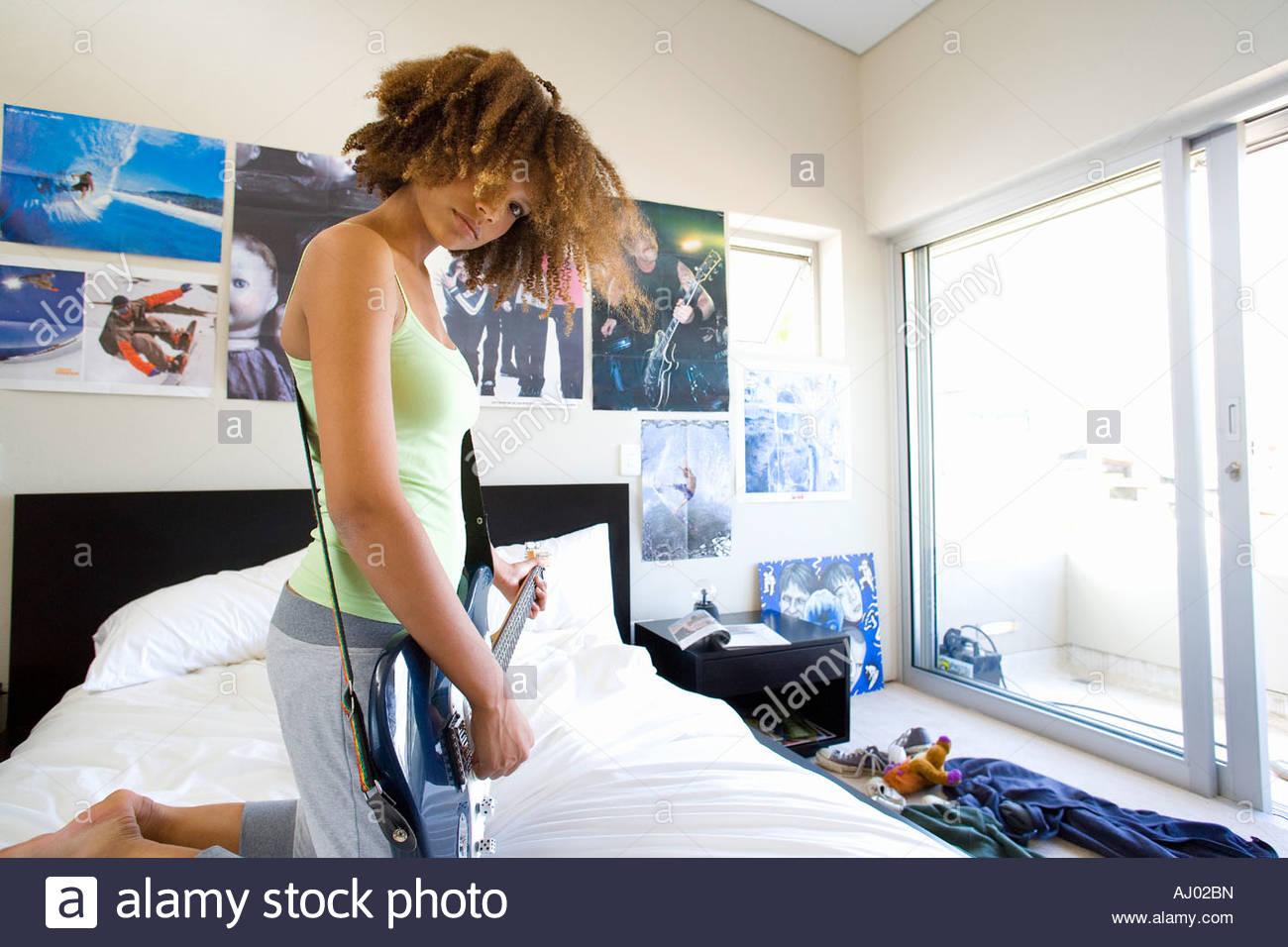 Stock Photo   Teenage girl playing electric guitar in bedroom  portrait. Teenage Girl Playing Electric Guitar In Bedroom  Portrait Stock