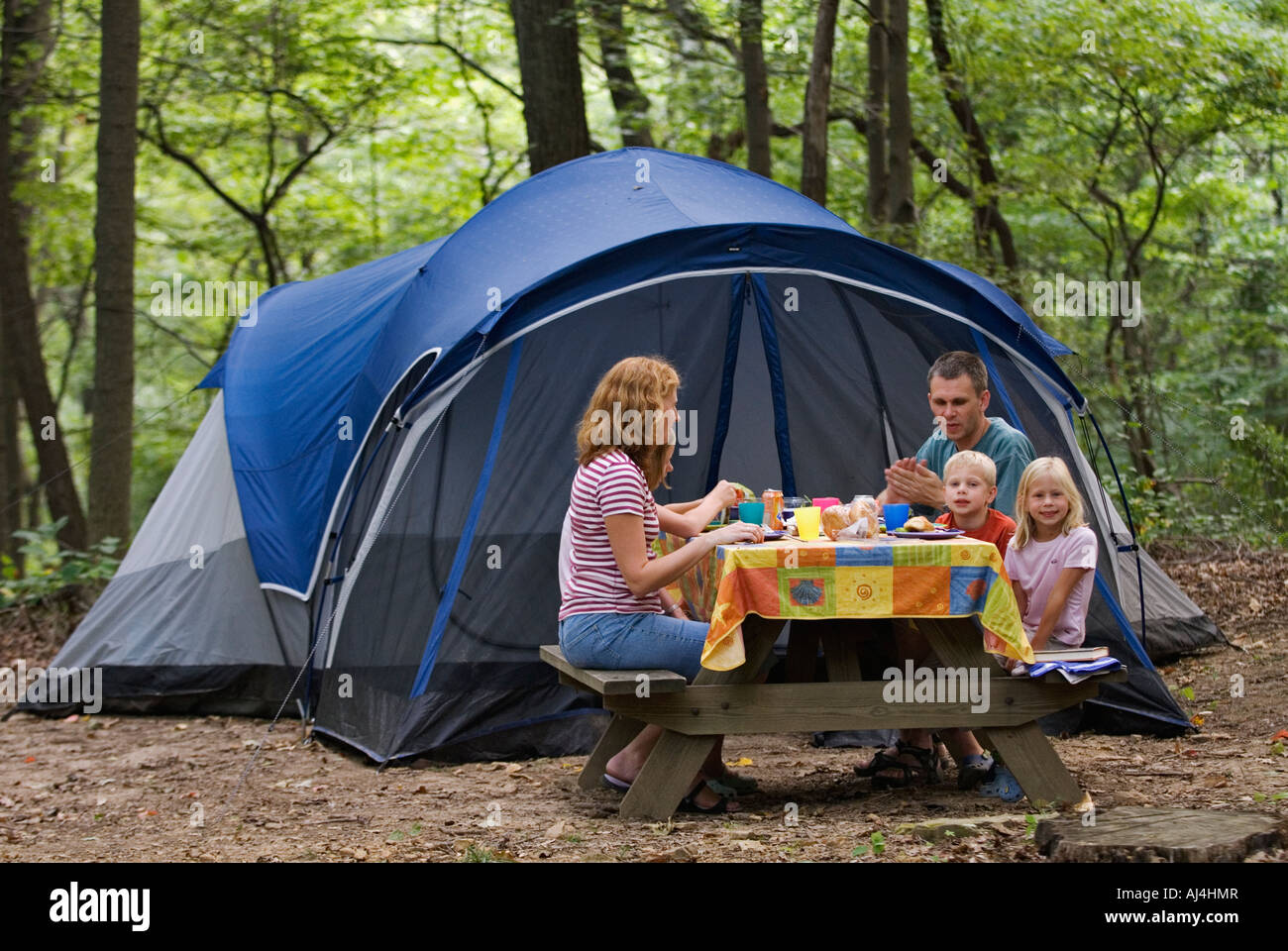 C&ing Family Eating Dinner at Picnic Table with Tent in the Background Ou0027Bannon Woods State Park Indiana  sc 1 st  Alamy & Camping Family Eating Dinner at Picnic Table with Tent in the ...
