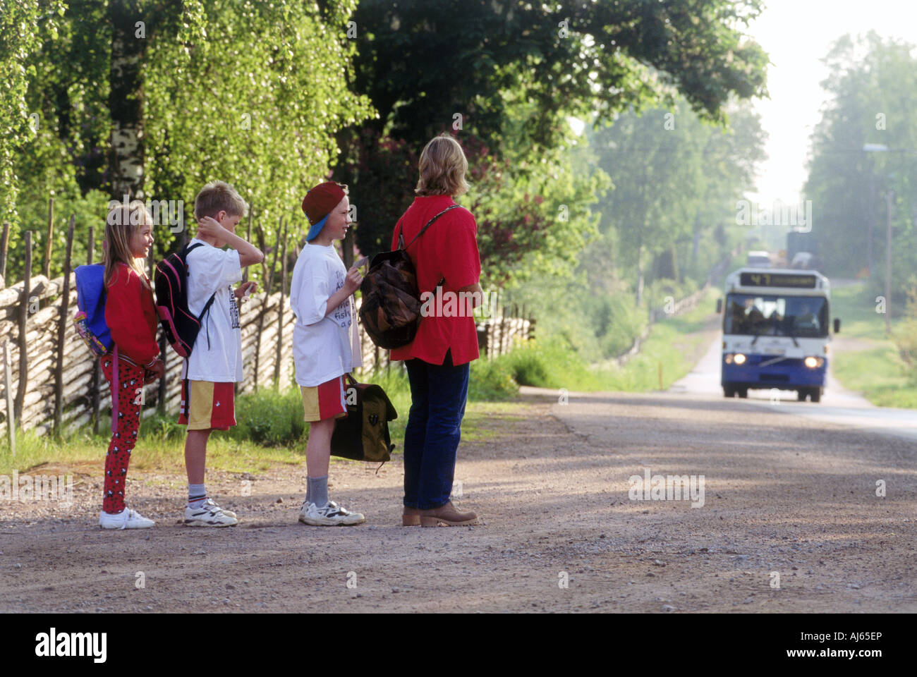 Children And Parent Waiting For School Bus On Country Road