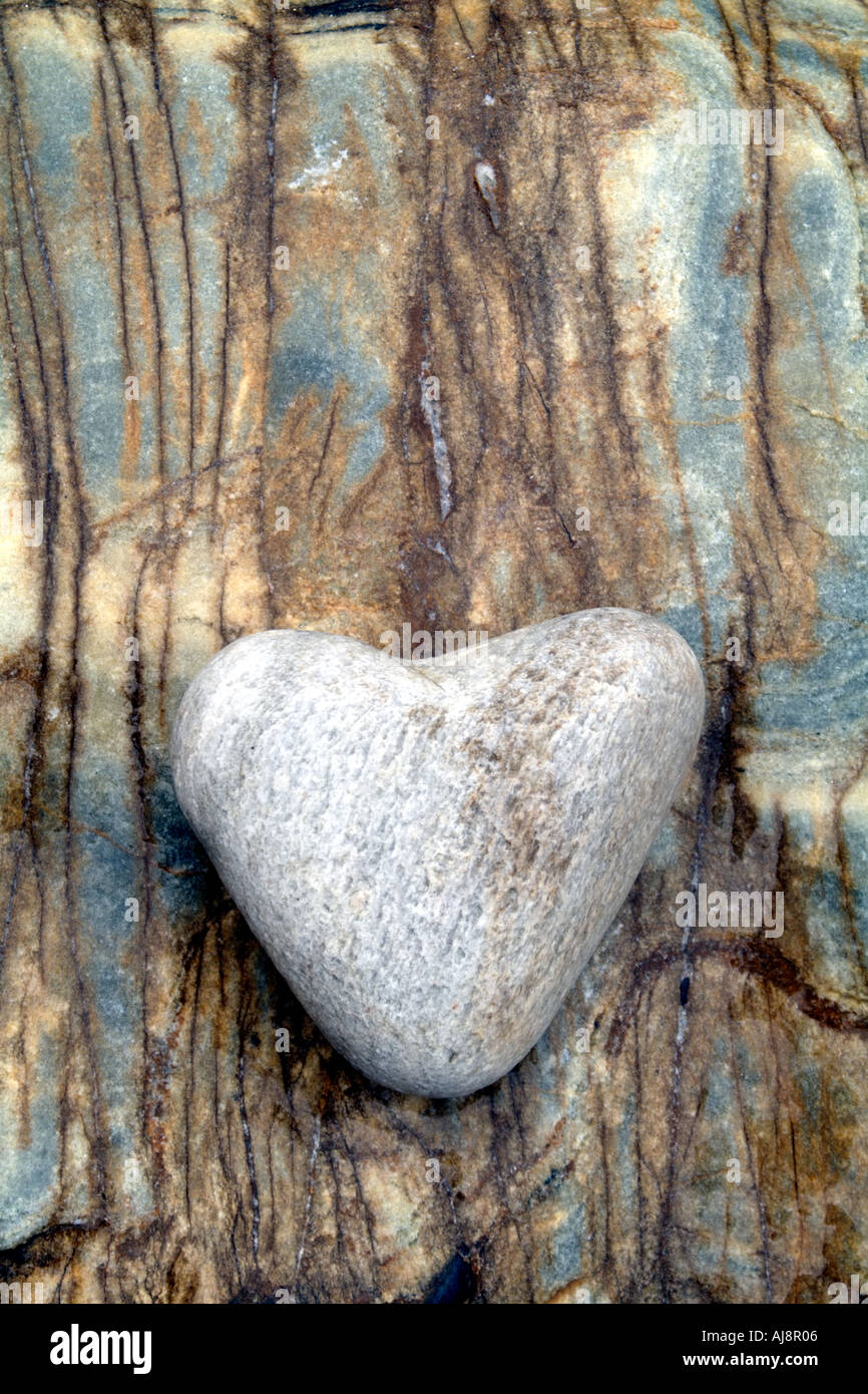 Smooth shaped white stones surface texture background stock photo - Smooth Heart Shaped Stone Against Veined Marble Rock Stock Image