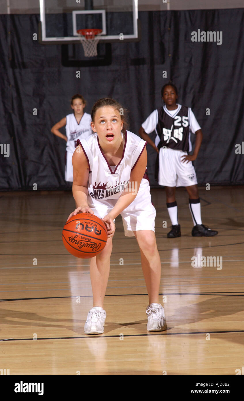 youth female basketball player prepares to shoot a foul shot at