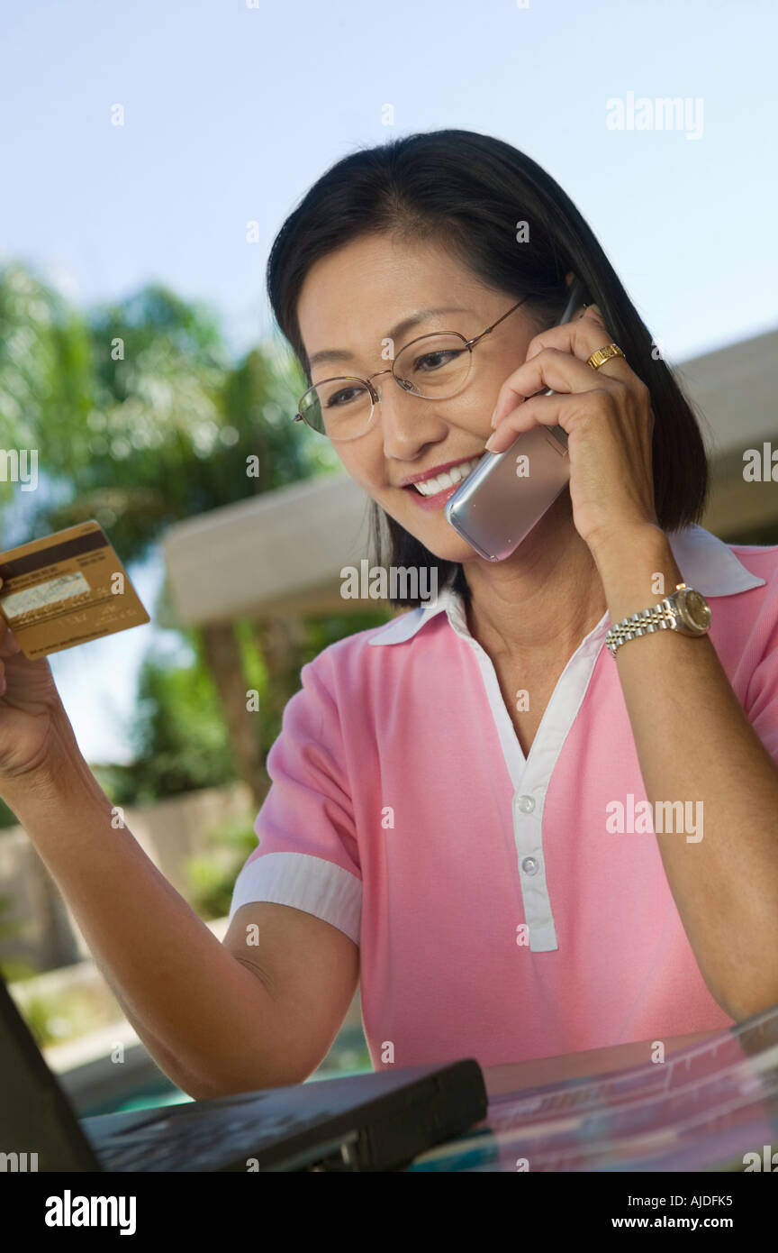 Woman Sitting At Backyard Table With Laptop Making Credit Card Purchase On  Cell Phone
