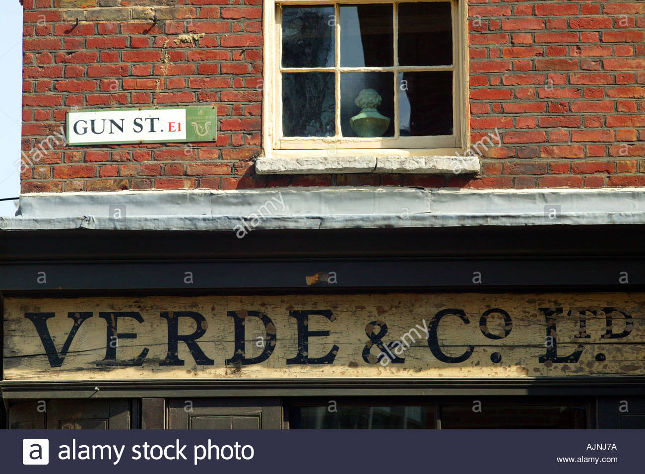old shop sign with road sign for gun street e1 east london