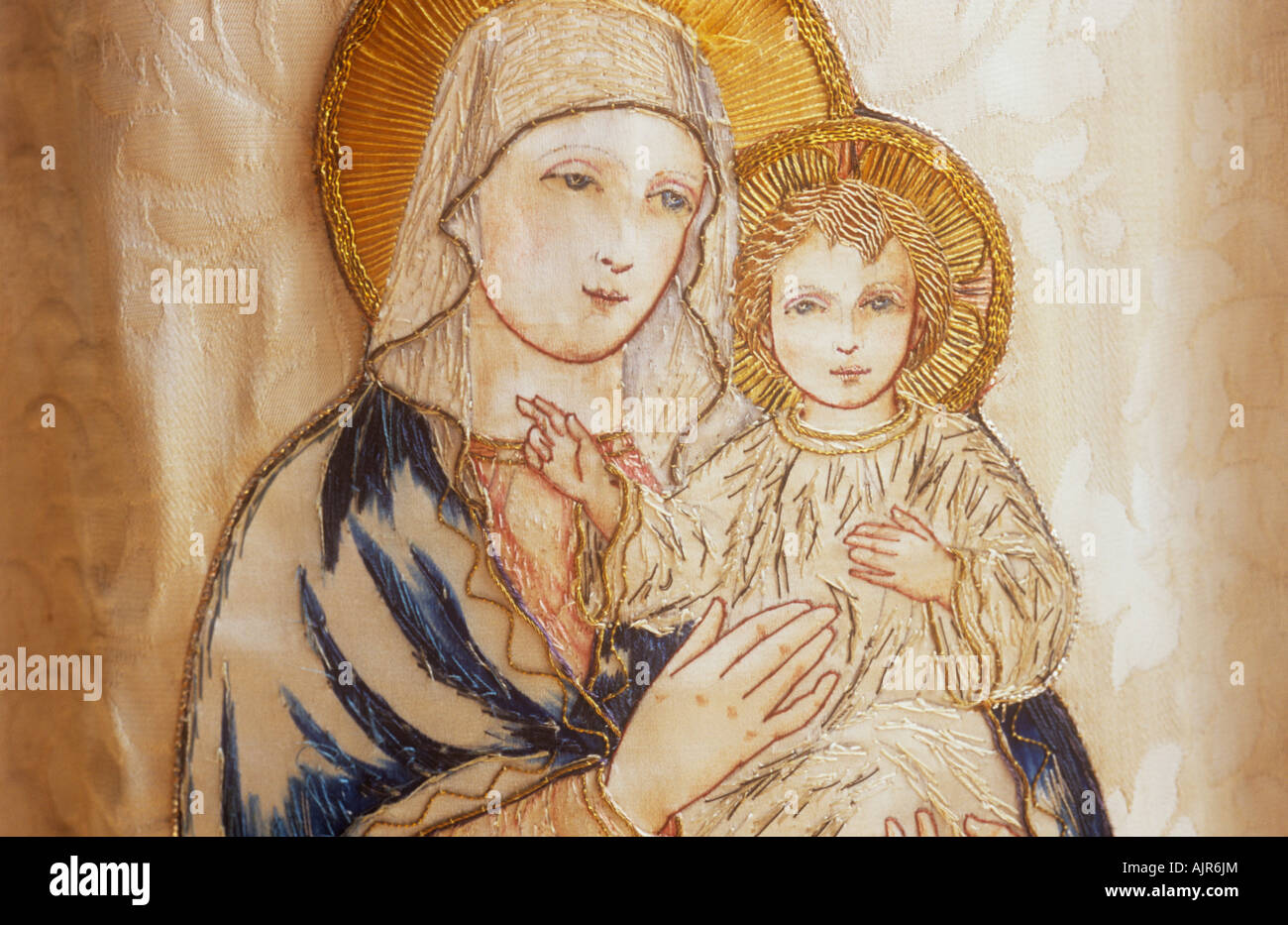 detail of embroidered image of virgin mary holding baby jesus