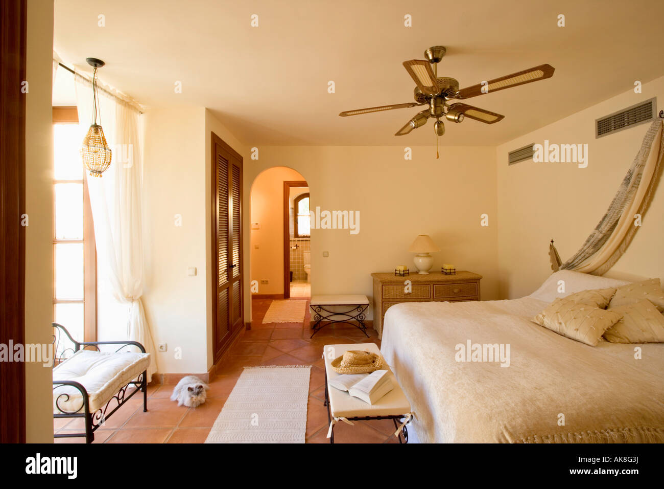 Ceiling Fan Above Bed With Cream Bedcover In Bedroom In Spanish Apartment