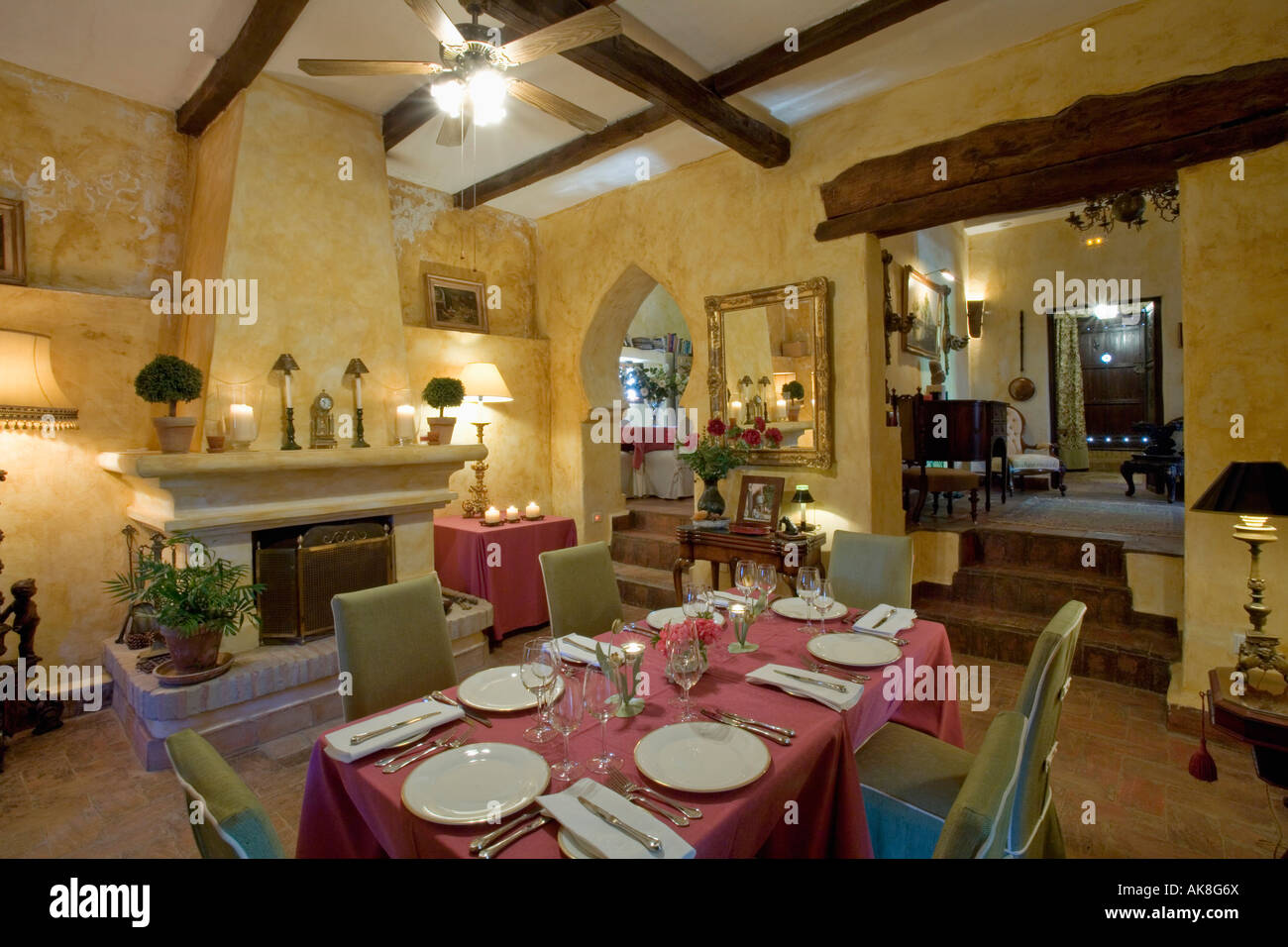 White crockery and red cloth on table in yellow dining room in ...