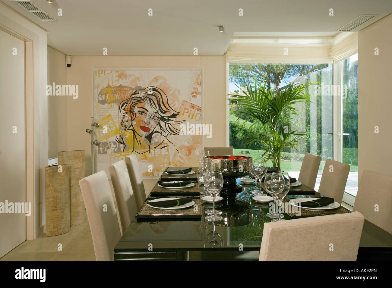 Modern Spanish dining room with large painting beside ...