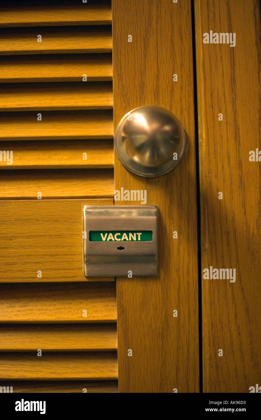 Bathroom Stall Knob vacant or unoccupied sign and brass knob on louvered door to