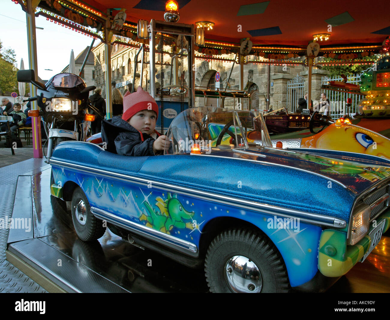 stock photo little child driving in a car of kids merry go round roundabout frth bavaria germany