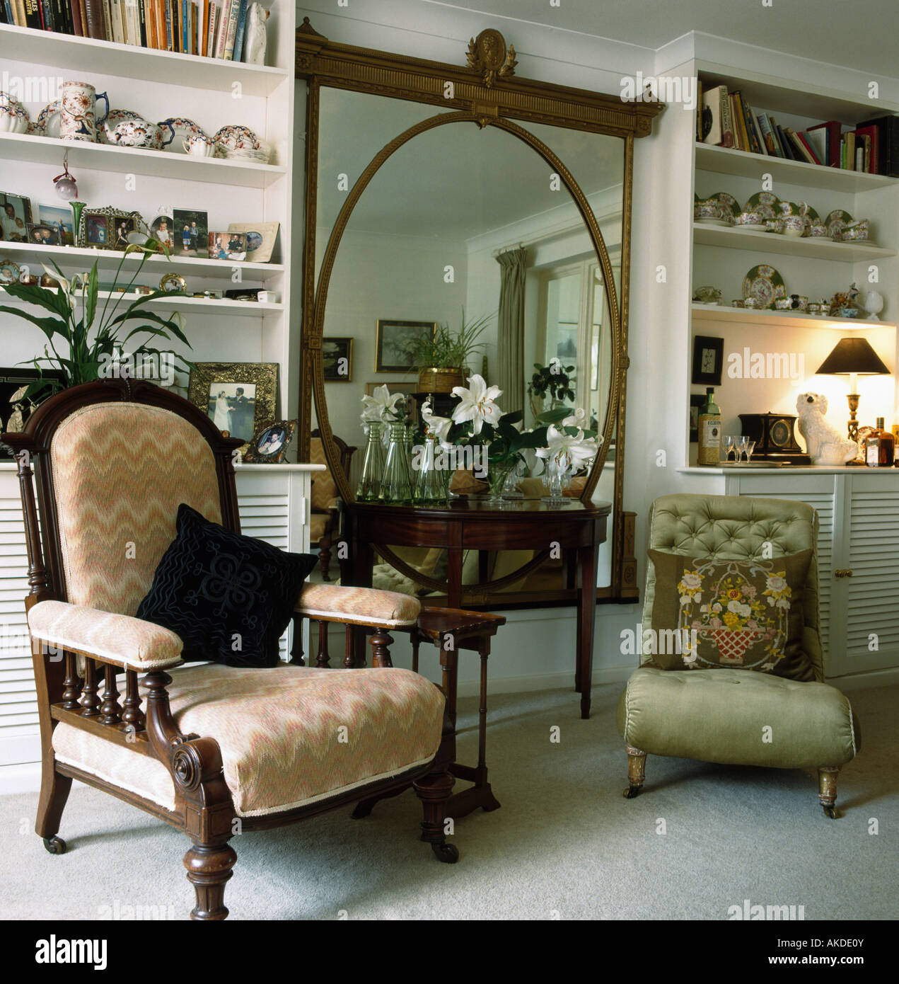 Edwardian Armchair And Small Green Victorian Chair On Either Side Of Console Table Below Large Antique Mirror In Living Room