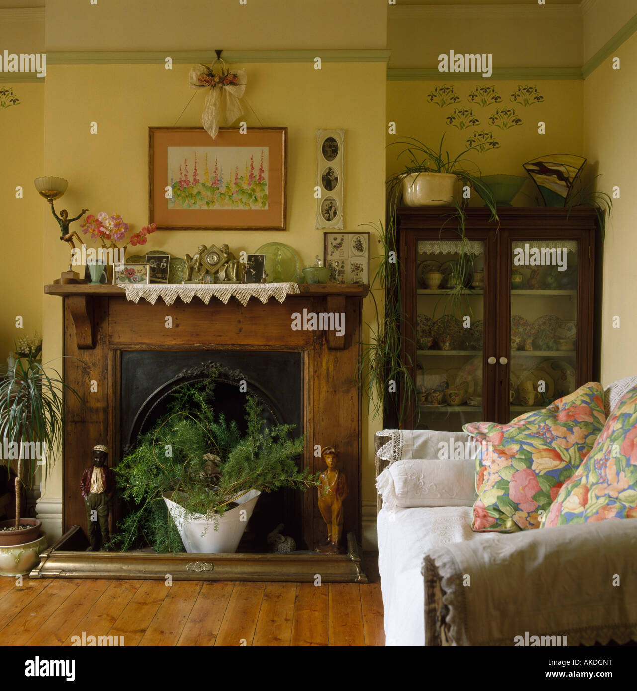 houseplants in fireplace with wooden mantelpiece in small yellow