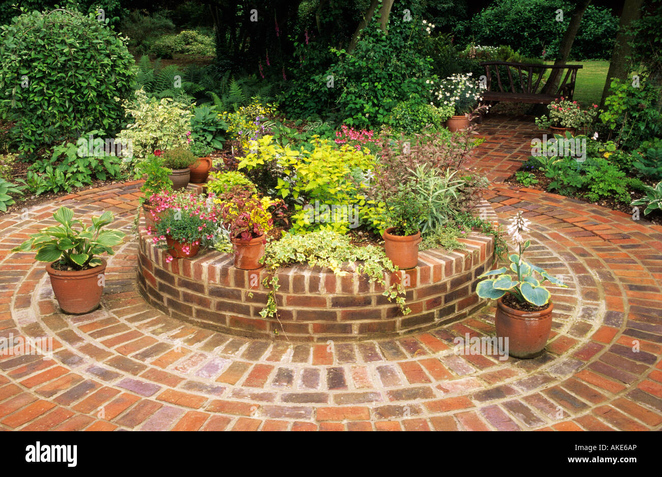 Stock Photo   Raised Circular Brick Seating And Pot Display Area In Patio  With Containers