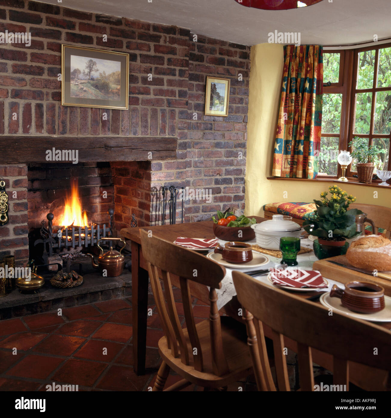 lighted fire in fireplace in exposed brick wall in cottage dining