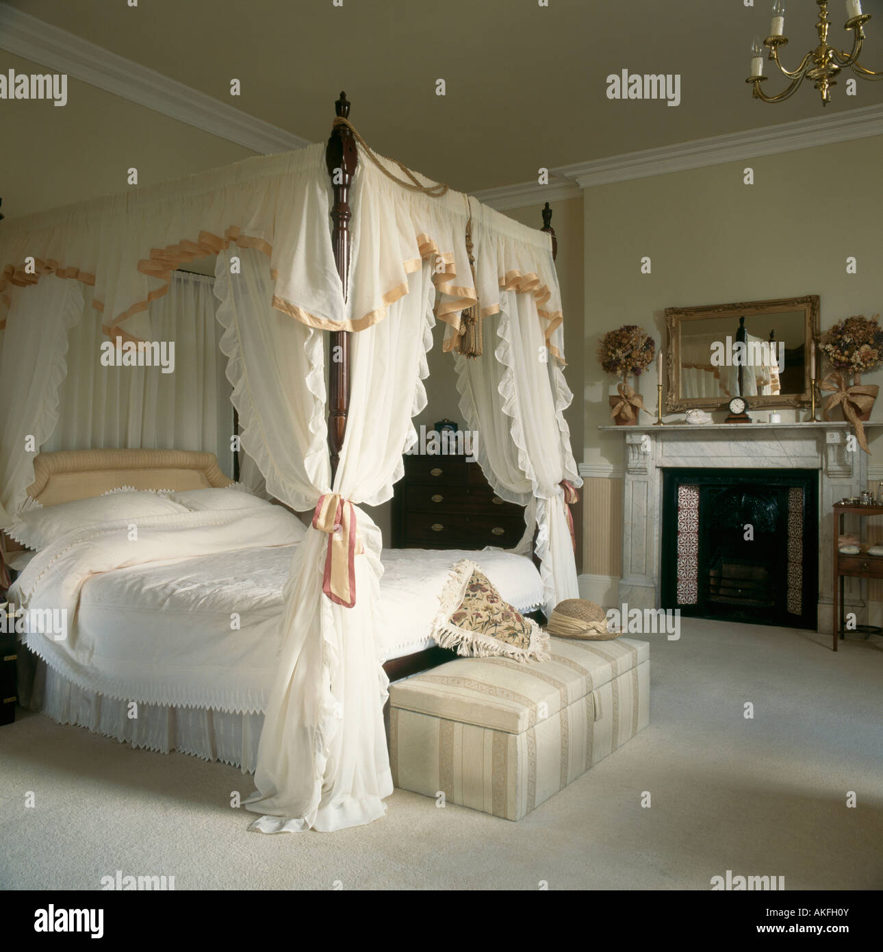 Silk edged white canopy and curtains on four poster bed with white linen in  bedroom with fireplace and grey carpet